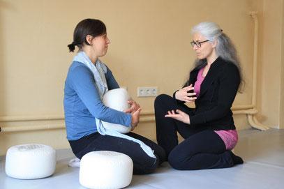 Eine Frau zeigt einer anderen etwas, eine Frau hält ein Yogakissen, beide sitzen auf dem Boden in einem Yogastudio oder Coachingstudio