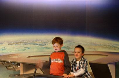 Lukas und Robin blicken vom Weltall auf die Erde.