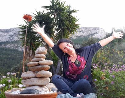 Kerstin Mais mit nach oben getreckten Armen vor dem Berg Montgo neben einem Steinmännchen