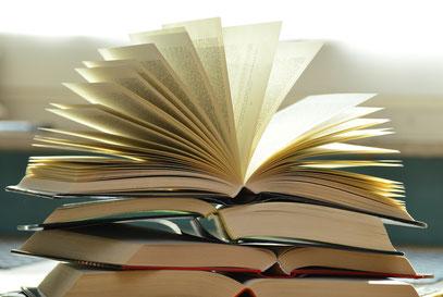 Ein Stapel aufgeschlagener Bücher: Lesen hilft dabei, gute Texte zu schreiben