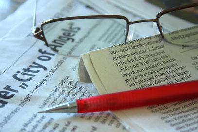 Auf einer Zeitung liegen eine Brille und ein Bleistift als Symbol für Pressearbeit.