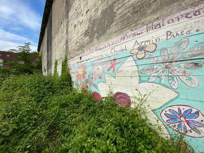 """Das Wandbild """"Blütenteppich"""" am Hochbunker an der Kattenturmer Heerstraße verwittert allmählich und wächst zu - Kunst im öffentlichen Raum in Bremen Obervieland (Foto: 05-2020, Jens Schmidt)"""