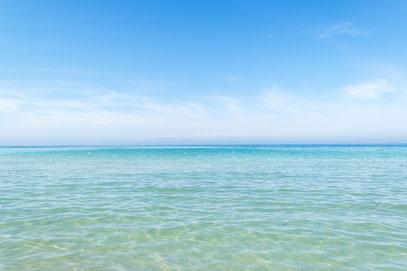 Bildausschnitt vom Meerwasser in Strandnähe, die Farbe ist vorne helltürkis und wird nach hinten dunkelblau. Der Himmel ist blau mit Schäfchenwolken.