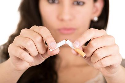 Eine Frau zerbricht eine Zigarette - Raucherentwönung gelingt mit Hypnose.