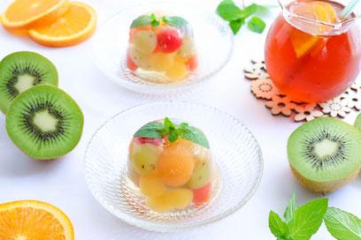 ピンクのノートパソコン。リングノートの上に置かれたクッキーの小皿。ボールペン。ミルクの入ったマグカップ。バラのブーケ。