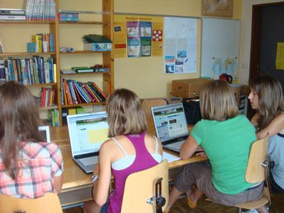 Rückansicht von Kindern, die an Laptops arbeiten.