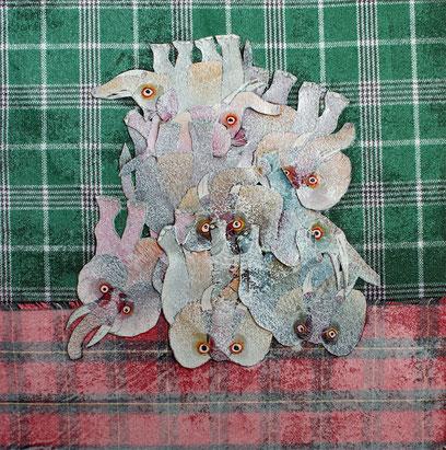 Trophées d'animaux tanzaniens découpés dans des Tinga Tinga empilés sur des tissus traditionnels.