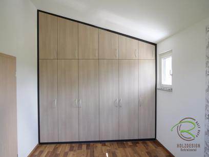 Dachschräge-Einbauschrank nach Maß für das Schlafzimmer, in hellem Holzdekor mit anthraziten Innenschränken mit Kleiderstangen und schrägen Schuhablagen