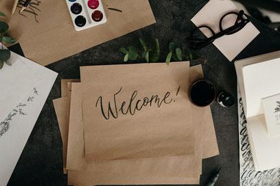 Auf einem Blatt Papier steht in künstlerischer Schrift Willkommen auf Englischer Sprache.