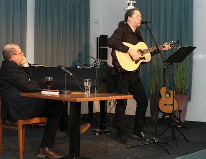 Zwei Künstler auf der Bühne: Matthias Schlicht liest, Daniel Fernholz musiziert.