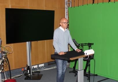 Andreas Narr in der Kulisse für Fernsehschalten. Aus Platzmangel im 80er-Jahre-Anbau beherbergt der Raum auch noch einen Radio-Sendeplatz. Bild: Johannes Thiede.