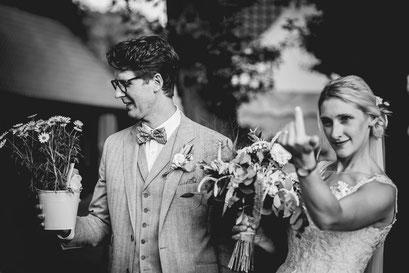 Sylvia und Marcel schauen verträumt in die Kamera. Sie halten zusammen den Brautstrauß