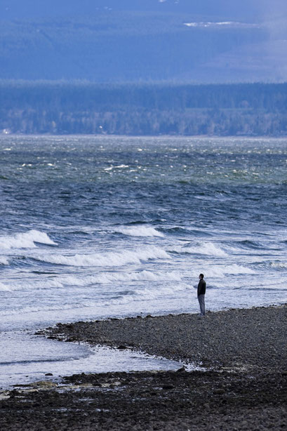 A lone man views the stormy waves in Comox.