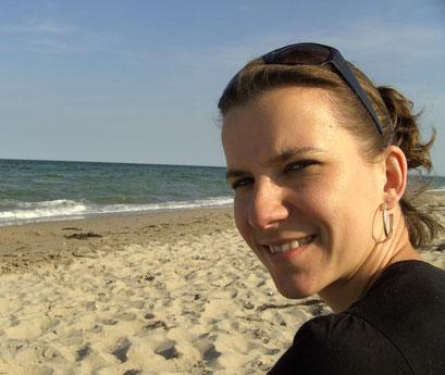 Frau sitzt am Strand der Ostsee und lächselt in Kamera
