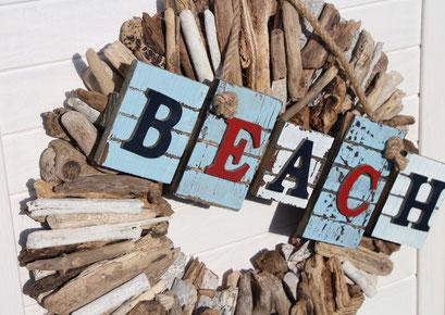Dekoidee: Holzkranz mit einem Beach Schild dekoriert.