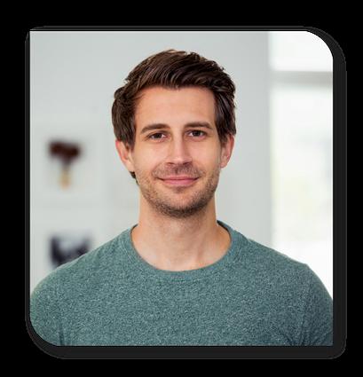 Portraitfoto von Claudio Weishaupt. Er grinst freundlich in die Kamera. Er hat kürzeres, dunkelbraunes Haar, welche locker nach hinten frisiert sind. Er hat einen dunklen 3-Tage-Bart und trägt ein grün meliertes Shirt.