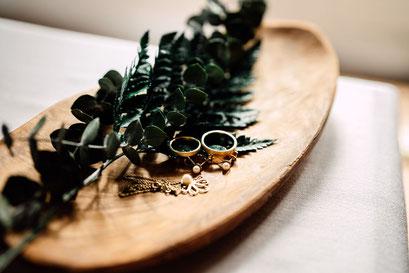 Auf einer Holzschale liegen Ringe, Ohringe und eine Kette. Es ist mit grünen Eukalyptus Pflanzen dekoriert.
