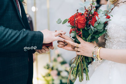Eine Braut steckt ihrem Bräutigam den Ehering an den Finger und hält mit der anderen Hand den Brautstrauß.