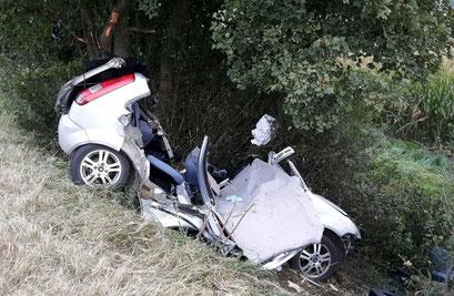 Die Unfallstelle mit zerstörtem PKW auf der K18. Foto: Polizei