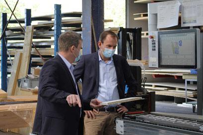 Geschäftsführer Ralf Fach (l.) erklärt Herrn Wagner die wasserfeste Bekantung der Platten mit PU.