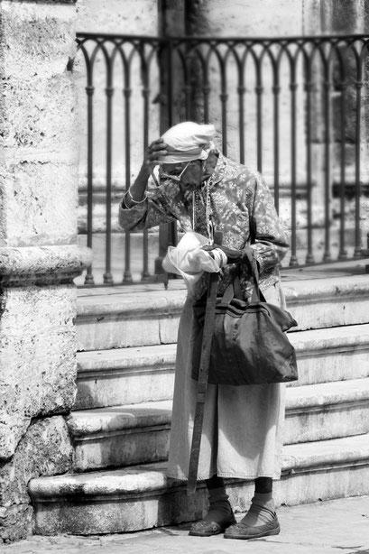Alte Frau mit langem Rock und Kopftuch, neben einer stehend, die rechte Hand auf dem Kopf, in der linken vor dem Körper ein zusammengekneueltes Tuch, überm Arm eine Tasche hängend