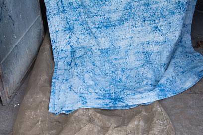 Après la teinture à l'indigo, le tissu nettoyé de la boue laisse apparaître un peu de bleu qui a réussi à imprégner le tissu en traversant la couche de boue.