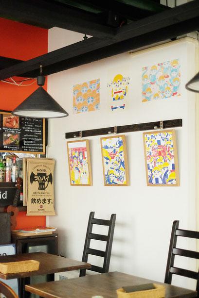 広島のイラストレーター、絵本作家、ミヤタタカシの絵本と絵の展示風景「カフェマルティッド」壁面にて