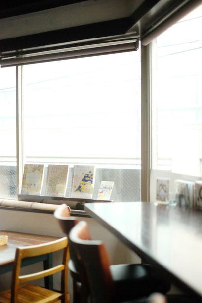 広島のイラストレーター、絵本作家、ミヤタタカシの絵本と絵の展示風景「カフェマルティッド」窓際にて