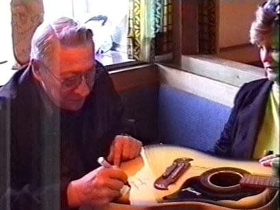 Scotty Moore setzt sein Autogramm auf eine Gitarre - Screenshot Elvis-Festival 2000, Elvis-Archiv Bad Nauheim