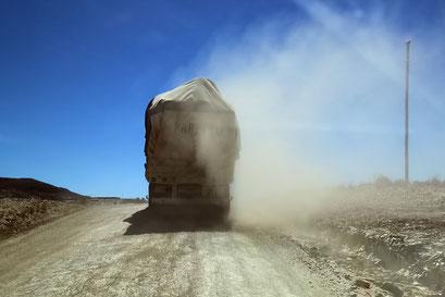 Staubige Aussichten hinter qualmenden Lastwagen