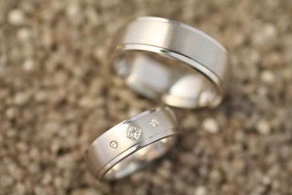 Trauringe / Eheringe aus gebürstetem Weißgold mit abgesetzten polierten Außenbereichen mit Prinzessdiamant und Brillanten