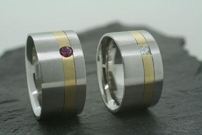 Trauringe / Eheringe aus Edelstahl im Bürst-Schliff mit Einlage aus Gelbgold und jeweils einem Rubin und Prinzessdiamant