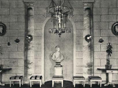 На задней стене, с центральной нишей для скульптуры, изображены монументальные мраморные колонны.