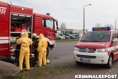 Feuerwehrleute rüsten sich mit Chemieschutzanzügen aus.|Foto: Christopher Sebastian Harms