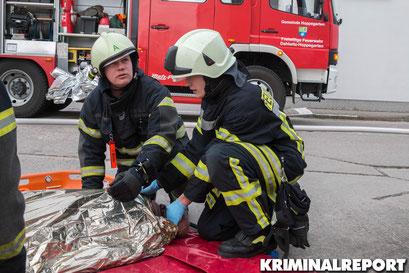 Zwei Feuerwehrmänner versorgen eine Person.|Foto: Christopher Sebastian Harms