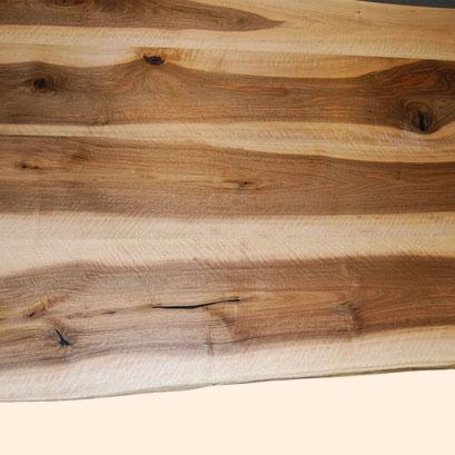 verleimte Platte aus Nussbaumholz, kräftiger Kontrast von Splintholz (hell) und Kernholz (dunkel), unten mit Naturkante