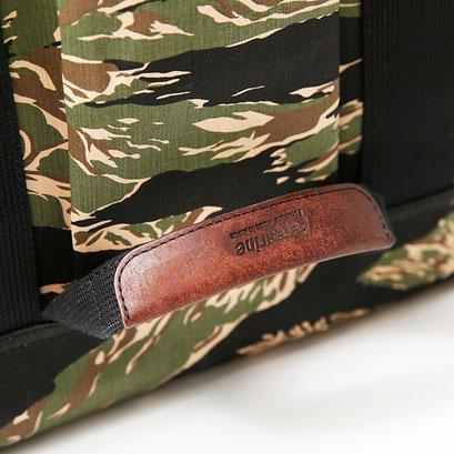 表面には革タグで巻いた持ち手を。重い荷物を入れた時などのサポート用として。