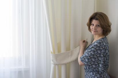 mueden.de, Gardinenservice, Bildvoh Hausfrau die an einer dekorierten Gardine steht