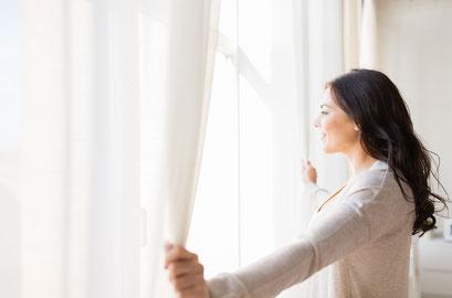 mueden.de, Gardinenservice, Bild Frau steht vor einem Fenster und schaut raus