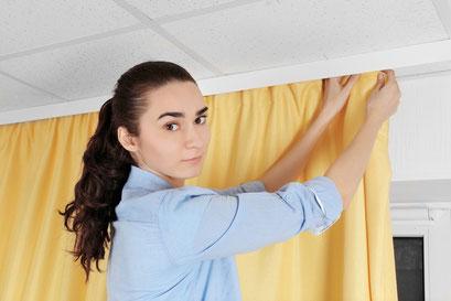 mueden.de, Gardinenservice, Bild von Frau mit hellblauer Blase, die gelbe Übergardinen aufhängt