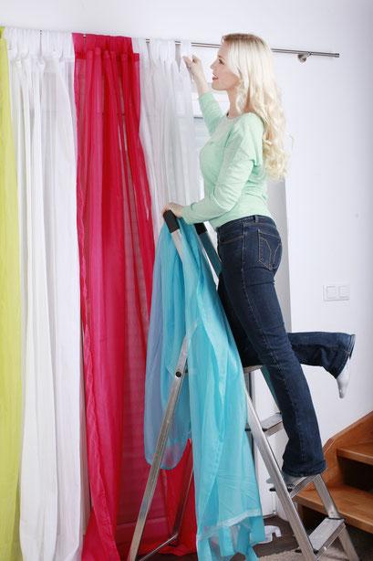 mueden.de, Gardinenservice, BildFrau steht auf Leiter und hängt bunte Stoffe auf