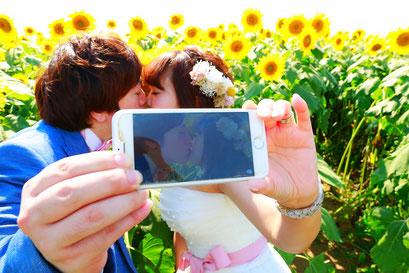 ひまわりウェディング スマホでキスシーンを撮影している新郎新婦の写真