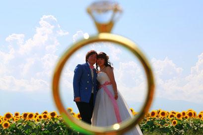 ひまわりウェディング リングオブジェの指輪の中に新郎新婦が入った遠近法の写真