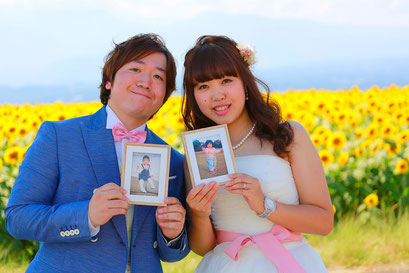 ひまわりウェディング ひまわりを背景に小さい頃の新郎新婦の写真額を手にもっての写真
