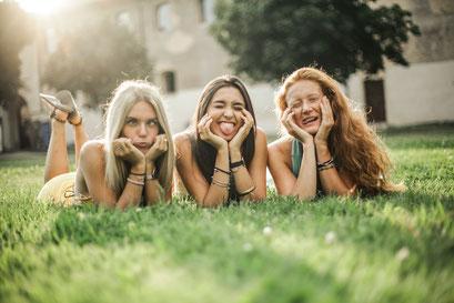 Freundinnen auf einer Wiese vor der Fotobox