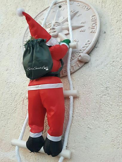 Babbo natale che sale la scala per portare i doni
