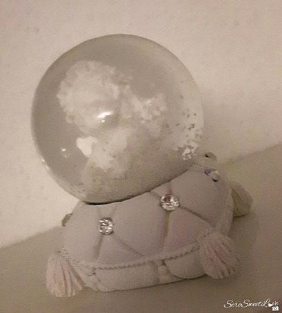 palla di vetro con angioletto sopra cuscino