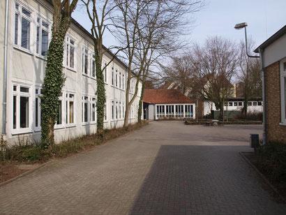 Unser Schulhof hinter dem Schulgebäude gelegen. Geradeaus sind der Schülertreff und die Sporthalle zu sehen.
