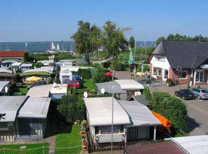 Blick aus Vogelperspektive auf einen Campingplatz mit Wohnwagen  mit Dümmer See im Hintergrund.