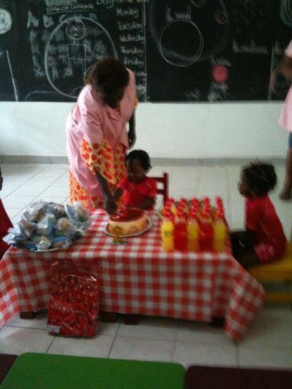 assistée par Mme Djengué, Emmanuelle coupe son gâteau